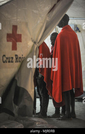 Malaga, Spain. 6th May, 2018. Migrants who were rescued from a dinghy in the Mediterranean Sea stand inside a tent of Spanish Red Cross after their arrival at Port of Malaga. Members of the Spanish Maritime Safety rescued in this early morning a total of 110 migrants from two boats near the Malaga coast. Credit: Jesus Merida/SOPA Images/ZUMA Wire/Alamy Live News - Stock Photo