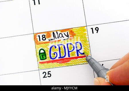 Woman fingers with pen writing reminder GDPR in calendar. Close-up. - Stock Photo