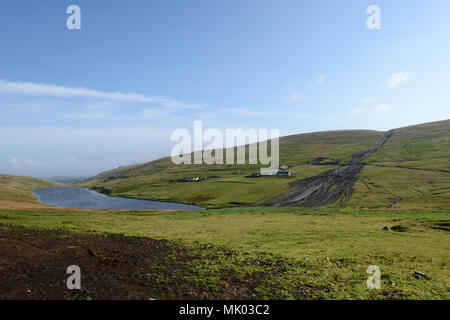 Peat landslide on the hills around a couple of house and settlements - Stock Photo