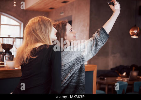 Two friends drinking coffee in a cafe, taking selfies with a smart phone and having fun making funny faces. Focus on the girl on the left - Stock Photo
