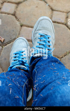 Person Standing  Wear Blue Jean With Seed Dirt Stuck on It and Blue Shoes - Stock Photo