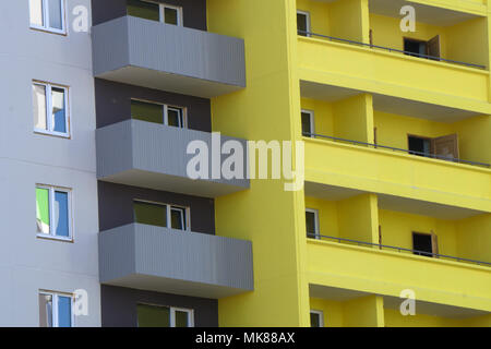 yellow colorful house walls and Windows with open decorated with fresh flowers - Stock Photo