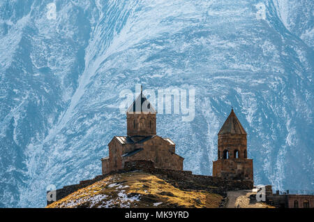 Caucasus mountains, ancient Gergeti Trinity church Tsminda Sameba against the glacier near mount Kazbek, landmark of Georgia - Stock Photo