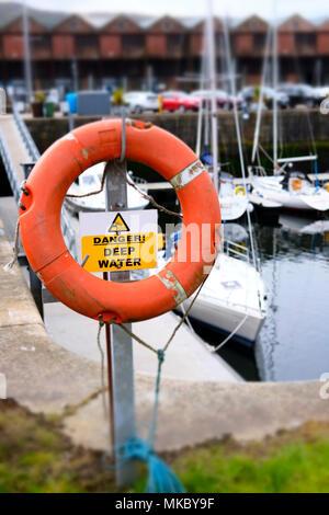Water safety life deep risk danger red orange buoy ring save swimmer dock harbour harbor coastal sea marina - Stock Photo