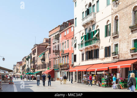 Busy pedestrian street scene in via Garibaldi, Castello, Venice, Veneto, Italy with local Venetians and tourists shopping at stores and a  Coop superm - Stock Photo