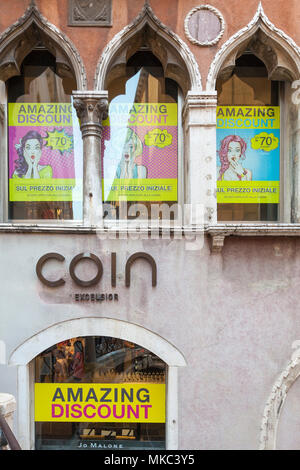 The sign on the historic Coin Excelsior Luxury Goods Store, Cannaregio, Venice, Veneto, Italy with Sale  posters in the windows. Closing down after a  - Stock Photo
