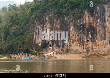 View of the Mekong River and limestone cliff where the famous Pak Ou Caves are set. They are located near Luang Prabang in Laos. - Stock Photo