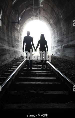 Couple walking hand in hand along the track through a railway tunnel towards the bright light at the other end, they appear as silhouettes against the - Stock Photo