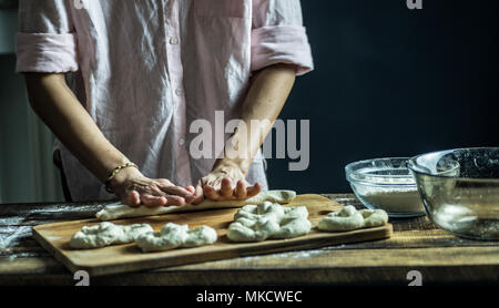 Dough dainted by the woman on the board - Stock Photo