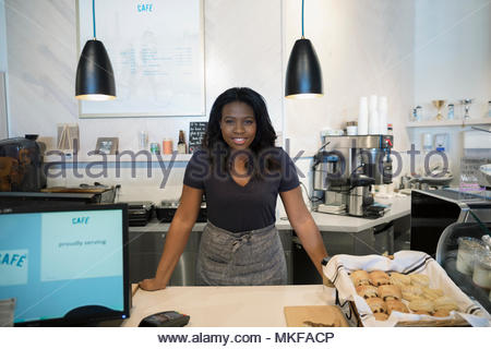 Portrait confident female small business owner working behind bakery counter - Stock Photo