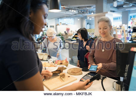 Senior woman with smart phone using contactless payment at bakery checkout - Stock Photo