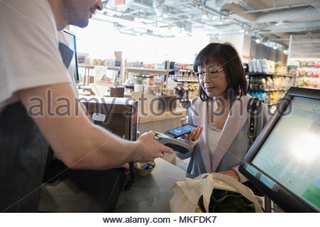 Worker helping active senior woman paying with smart phone contactless payment at grocery store checkout - Stock Photo