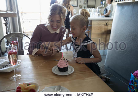 Mother and daughter with smart phone celebrating birthday at cafe - Stock Photo