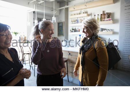 Happy senior women friends talking in cafe - Stock Photo