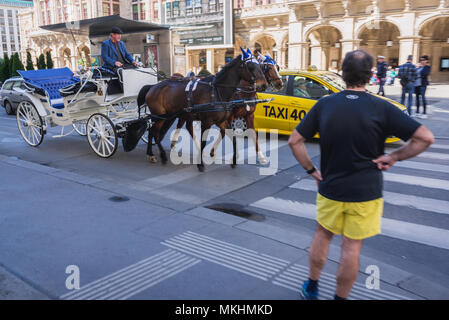 Horse-drawn carriage called Fiaker in front of Vienna State Opera in Vienna, Austria - Stock Photo