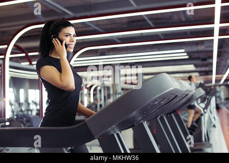Fit business woman talking on smartphone while running on treadmill - Stock Photo
