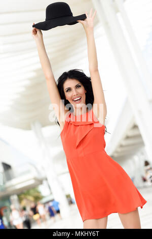 Brunette woman wearing orange short dress and sun hat in the street. Young girl with curly hairstyle standing in urban background - Stock Photo