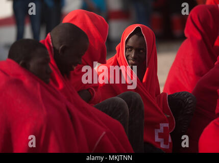 Malaga, Spain. 8th May, 2018. A migrant, who was rescued in the Mediterranean Sea from a dinghy, chats covered by red blanket after his arrival at Malaga port during the World Red Cross day. Aboard of a boat, members of the Spanish Maritime Safety rescued a total of 57 migrants (of them, 10 womens and two possible minors) near the Malaga coast and brought at Port of Malaga, where they were assisted by the Spanish Red Cross. Credit: Jesus Merida/SOPA Images/ZUMA Wire/Alamy Live News - Stock Photo