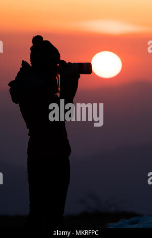 Young women photographer trying to capture the sunrise through her camera - Stock Photo