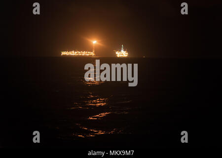FPSO tanker vessel near Oil Rig at night. Offshore oil and gas industry - Stock Photo