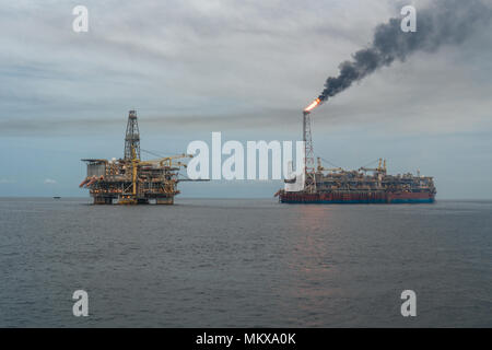 FPSO tanker vessel near Oil Rig platform. Offshore oil and gas industry - Stock Photo