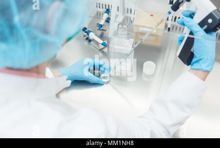 Scientist in lab conducting biotechnological experiment  - Stock Photo