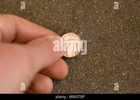 Posed picture of picking up a one pence piece from the ground. UK - Stock Photo