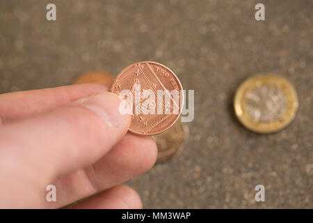 Posed picture of picking up a two pence piece with other coinage behind. UK - Stock Photo