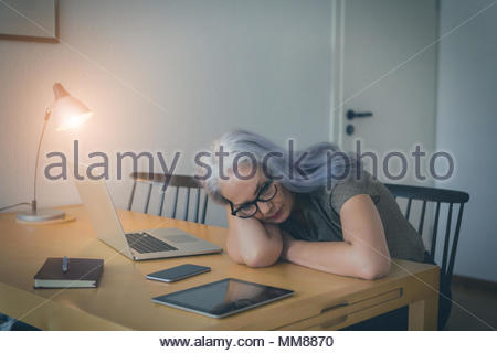 Tired elderly woman working overtime by lamplight in an office resting her head on her arms as she takes a break - Stock Photo