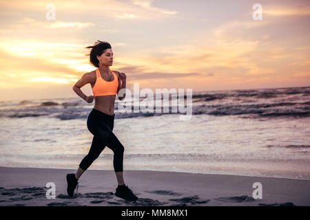 Woman athlete running along the beach in the morning. Woman in running outfit sprinting on the sea shore. - Stock Photo