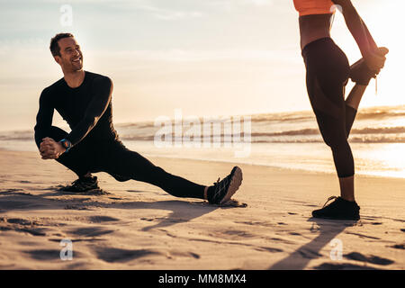 Young people exercising on the beach in morning. Runner stretching and warming up along the sea shore and having a chat. - Stock Photo