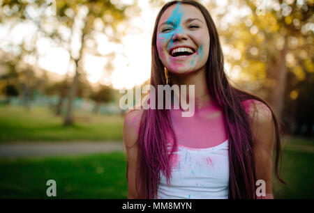 Beautiful woman with colored powder smeared on her face. Smiling girl playing with colors during holi festival at park. - Stock Photo