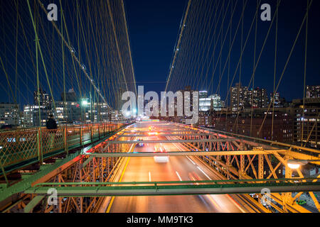 Long exposure picture of cars passing over the illuminated Brooklyn Bridge at night. Manhattan skyline in the background, New York city, USA. - Stock Photo