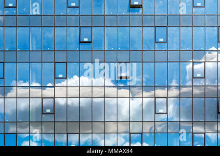 Cloudy sky reflected in the windows of modern office building. Urban abstract background - Stock Photo