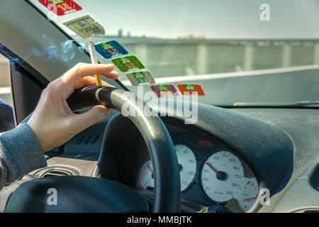 Smoking while driving a car on the highway, interior view and copy space, France. - Stock Photo