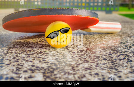 Tennis table paddle with a smiley ball below it on a stone tennis table in a park. Loving sport concept. - Stock Photo