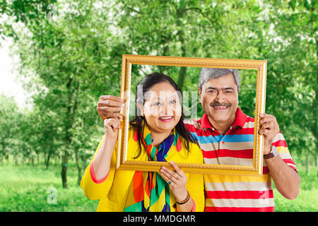 Happy Two Senior Couple holding picture frame Over face. In Garden - Stock Photo