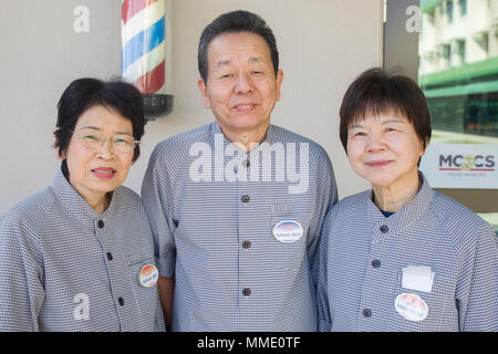 Chieko Murakami, left, Hisato Murakami, center, and Tomie Shigemura, barbers working at Marine Corps Air Station Iwakuni, Japan, pose in front of the Torii Pines barber shop at the air station, Oct. 25, 2017. They are currently three of the oldest employed Japanese workers on base. Shigemura began working in 1970, and Hisato and his wife, Chieko, joined her a year later. After nearly half a century, these barbers have whizzed their clippers through the hairs of countless Marines. From the dog days of the Vietnam War to the ongoing War on Terror, they've buzzed their way through time at MCAS Iw - Stock Photo