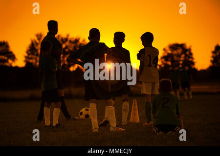 Sunset Soccer. Kids Soccer Football Team on Training with the Coach. Sports Soccer Practice at Sunset. Soccer Summer Camp for Sporty Children - Stock Photo