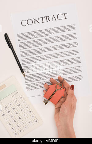 top view of cropped hand holding key from house over contract isolated on white - Stock Photo