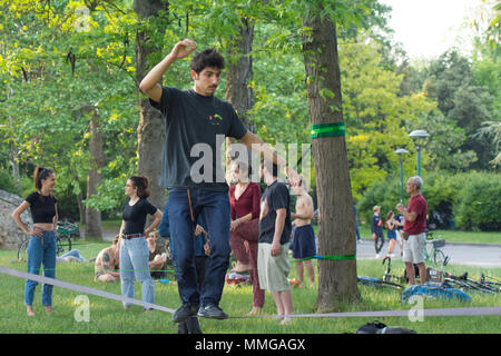 front view of a black haired young man on the slackline, slacklining - Stock Photo