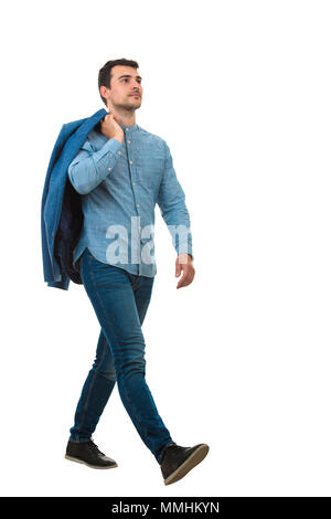 Side view of a proud young businessman carrying his jacket on back over his shoulder, walks isolated on white background. - Stock Photo