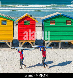 Smiling young South African surfers carrying their surfboards on the beach of Muizenberg, famous for the colorful beach huts, South Africa. - Stock Photo