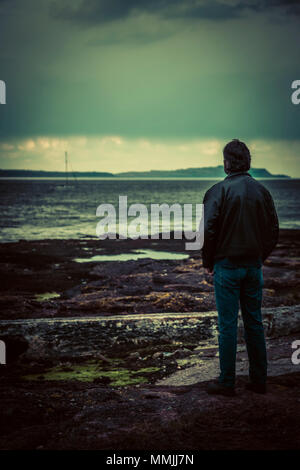 near silhouette of a man wearing a  leather jacket, looking out over  the rocky shoreline, gathering storm - Stock Photo