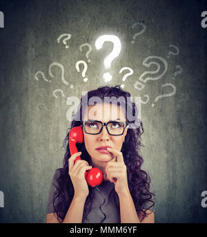 Misunderstanding and distant call. Upset worried confused woman talking on a phone has many questions isolated on gray background. - Stock Photo