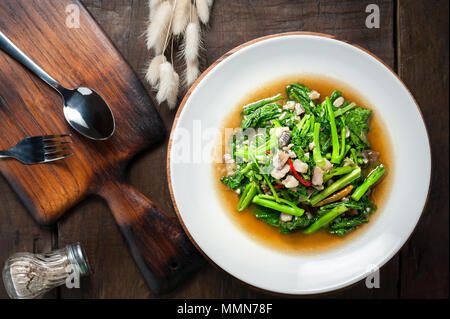 Thai food : Stir-fried kale with sun-dried salted fish on wooden table - Stock Photo