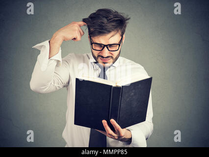 Young confused man scratching head while trying to read smart book misunderstanding content. - Stock Photo