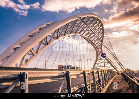 A steel bridge for cars and people in the Garbatella district in Rome at sunset - Stock Photo
