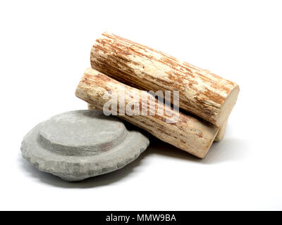 Thanaka wood and Kyauk pyin stone slab on white background (Isolated background). The Tanaka is popular with Burmese women. The face to make a beautify - Stock Photo