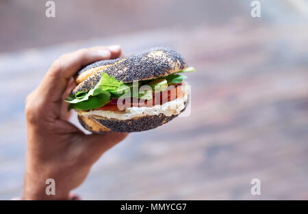 Man holding a delicious cream cheese and salmon bagel - Stock Photo